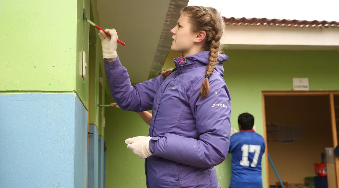 Joven voluntaria pinta un muro para renovar una primaria durante su voluntariado social en Perú.